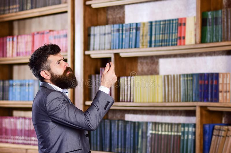 Mature man with serious face. Professor stands in big library and choose book. Bearded man in expensive suit in his cabinet. Study, learn, teach, history royalty free stock photo