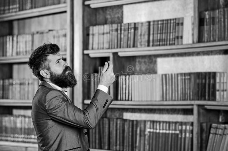 Mature man with serious face. Professor stands in big library and choose book. Bearded man in expensive suit in his. Cabinet. Study, learn, teach, history stock images