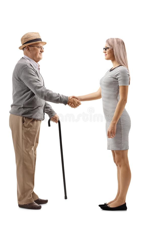 Mature man shaking hands with a young woman stock images