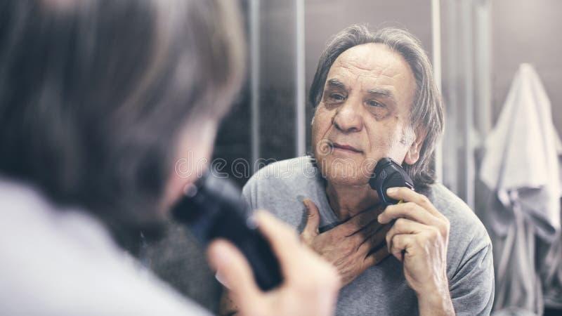 Mature man shaving in front of mirror. Mature man shaving in front of  mirror royalty free stock images