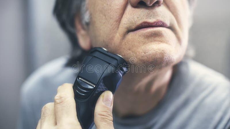 Mature man shaving in front of mirror. Mature man shaving in front of  mirror royalty free stock photo