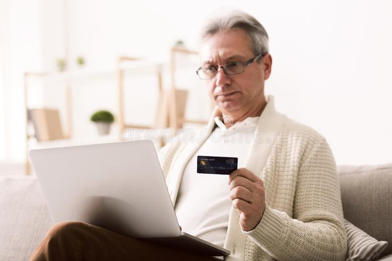 Mature man shopping online on laptop, using credit card. At home royalty free stock photography