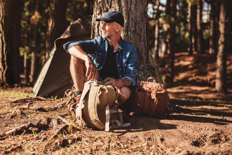 Mature man sitting alone at campsite with backpack. Portrait of senior man sitting under a tree with a backpack. Mature man sitting alone at campsite in forest stock image