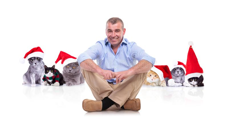 Mature man sitting cross-legged in front of christmas cats stock photography