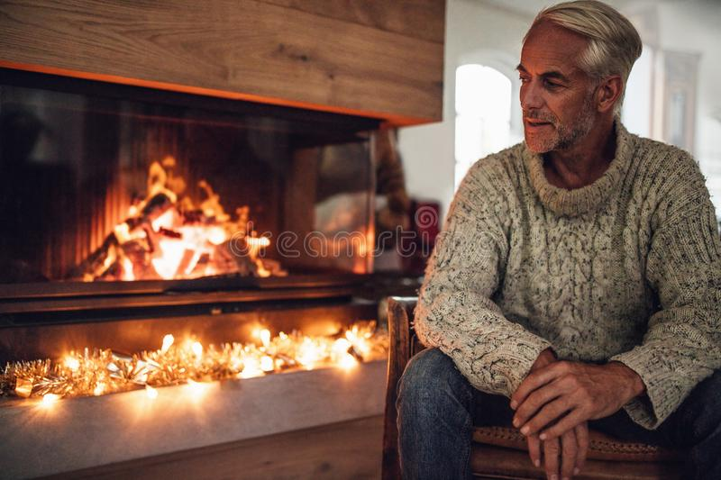 Mature man sitting by fire place in living room stock photography