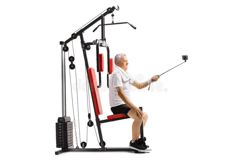 Mature man sitting on a multifunctional exercise machine and taking a selfie with a stick. Isolated on white background royalty free stock photography
