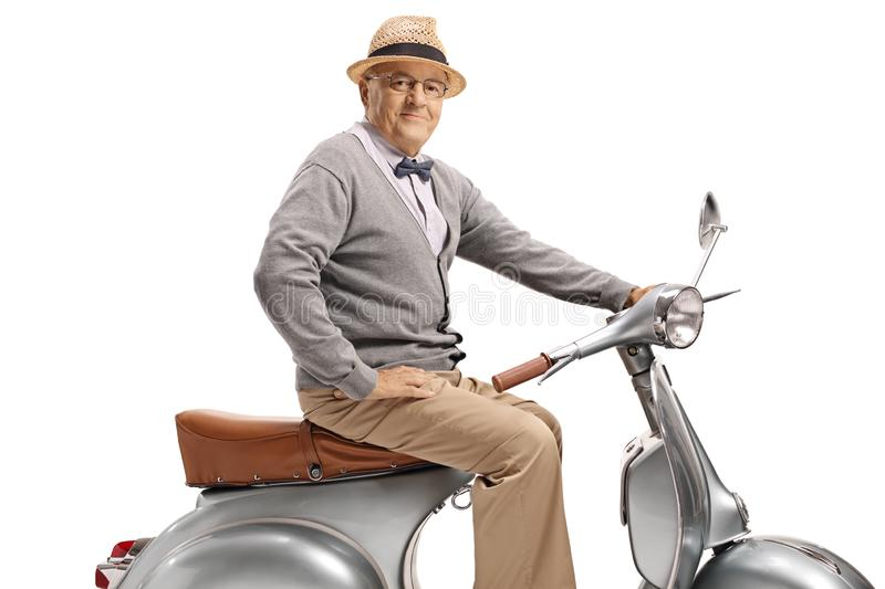 Mature man sitting on a vintage scooter royalty free stock images