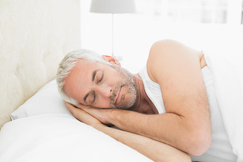 Mature man sleeping in bed. Closeup of a mature man sleeping in bed at home royalty free stock photos