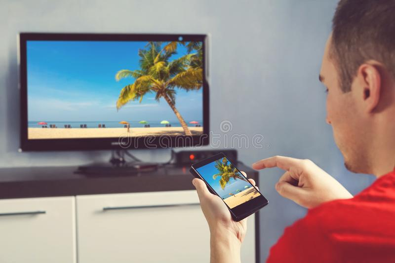 Mature Man With Smartphone Connected To A TV Watching Movie At Home. Relaxed man with smartphone connected to a tv and envisioning photos in networking royalty free stock photography
