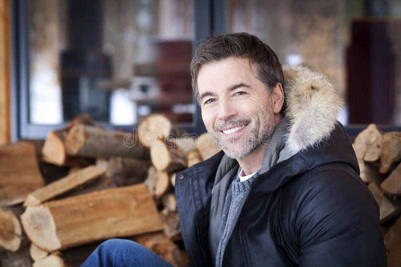 Mature man smiling at the camera. At the country house royalty free stock images