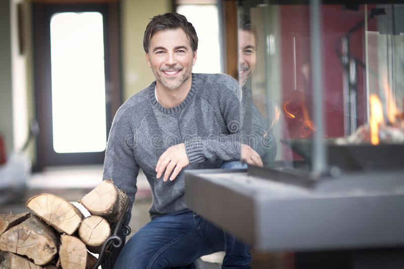 Mature man smiling at the country house. At the Fireplace royalty free stock image
