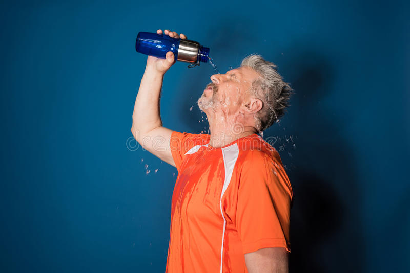 Mature man in sportswear pouring water from sports bottle on face royalty free stock photos