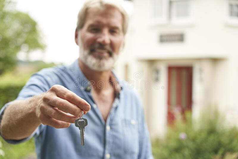 Portrait Of Mature Man Standing In Garden In Front Of Dream Home In Countryside Holding Keys royalty free stock images