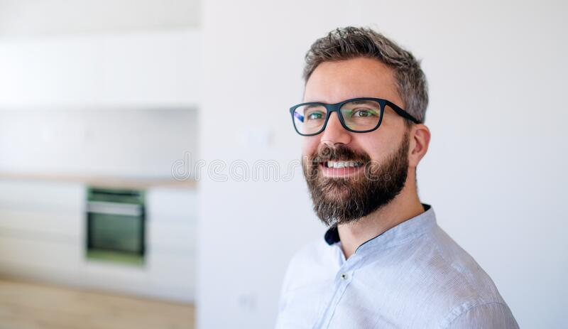 Mature man standing in house, moving in new home concept. royalty free stock photography