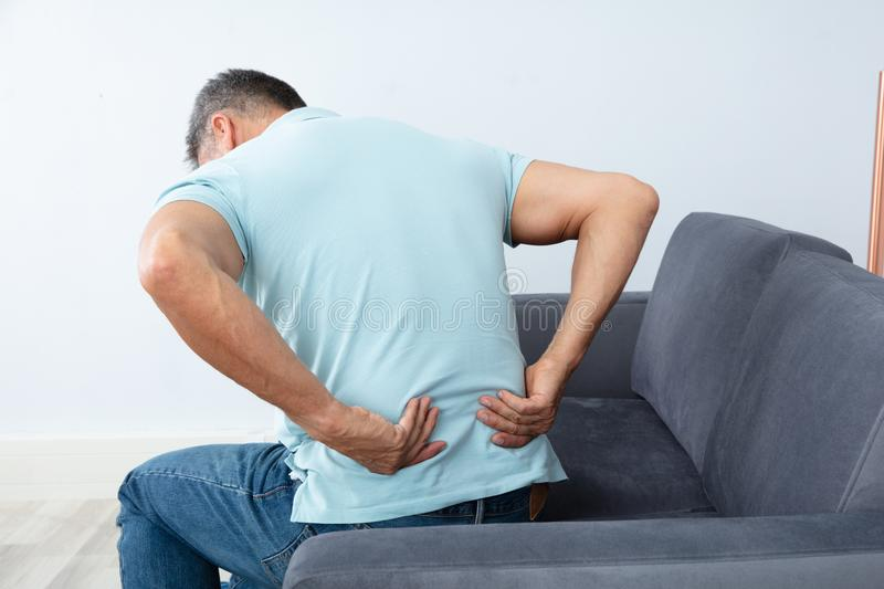 Mature Man Suffering From Back Pain. Mature Man Sitting On Sofa Suffering From Back Pain stock photo
