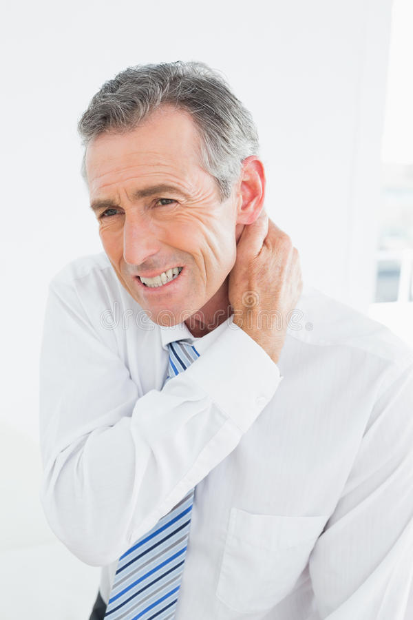 Mature man suffering from neck pain stock image