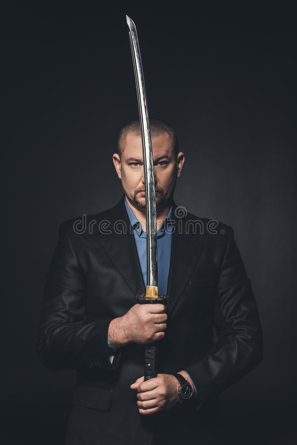mature man in suit holding japanese katana sword in front of his face royalty free stock photography