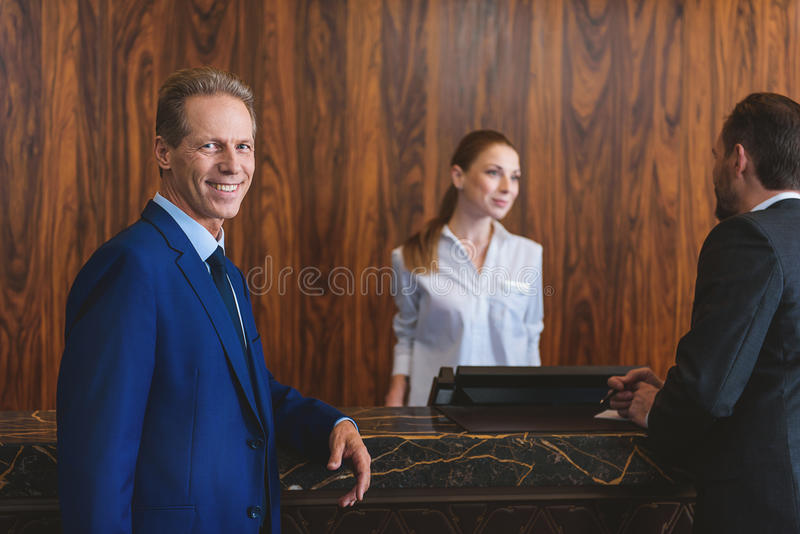 Mature man in suit waiting in hotel stock photography