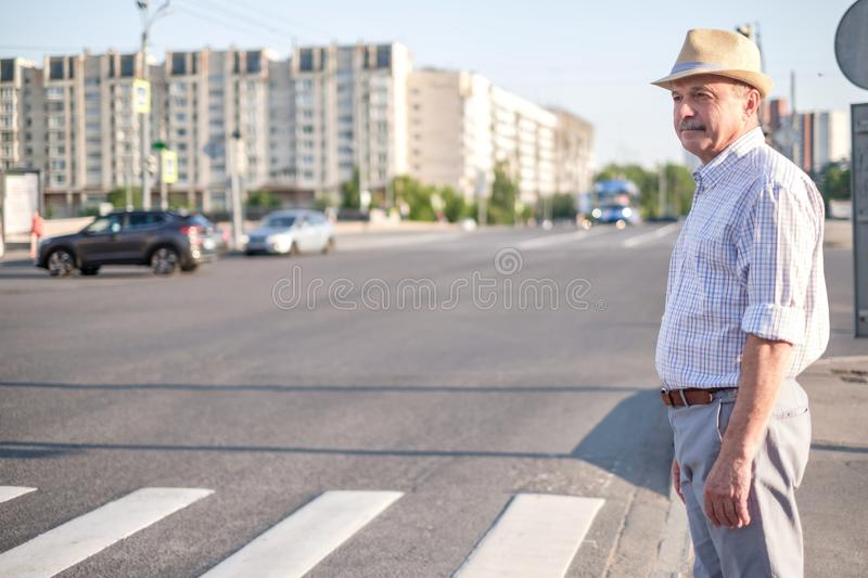 Mature european man waiting to cross street. Mature man in summer hat waiting to cross street on sunny day stock image