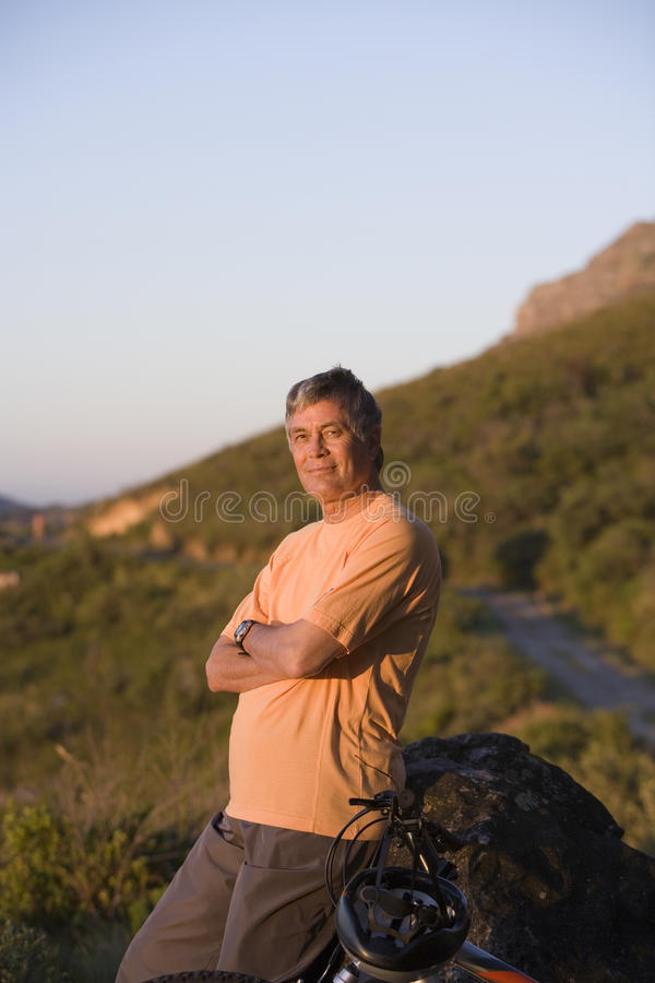 Mature man taking break from cycling on mountain trail, standing beside rock, arms folded, looking at scenery royalty free stock images
