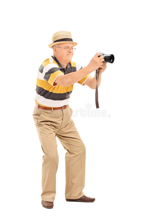 Mature man taking a picture with a camera. Full length portrait of a mature man taking a picture with a camera isolated on white background stock photos
