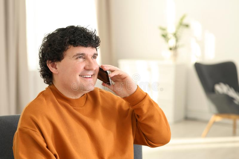 Mature man talking on mobile phone indoors. stock photography