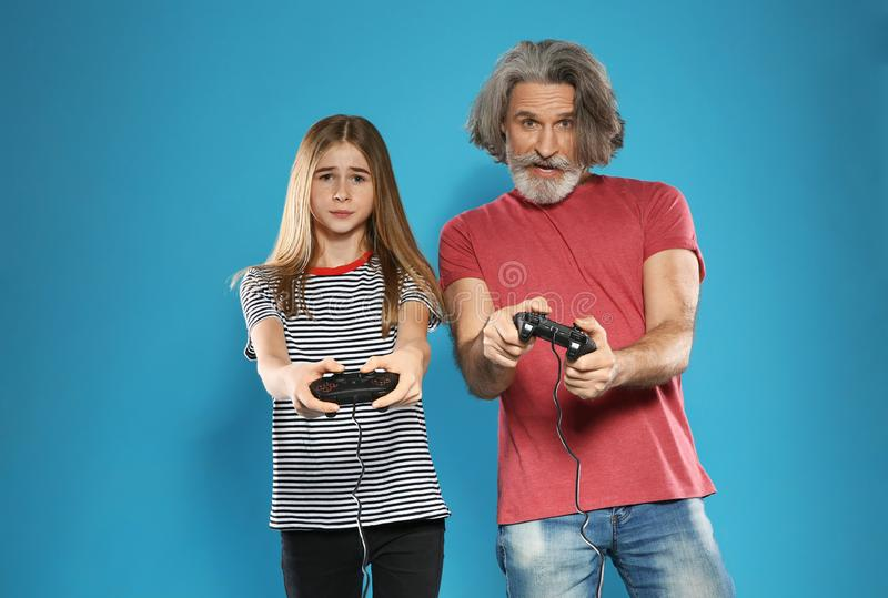 Mature man and teenage girl playing games with controllers on color background stock images