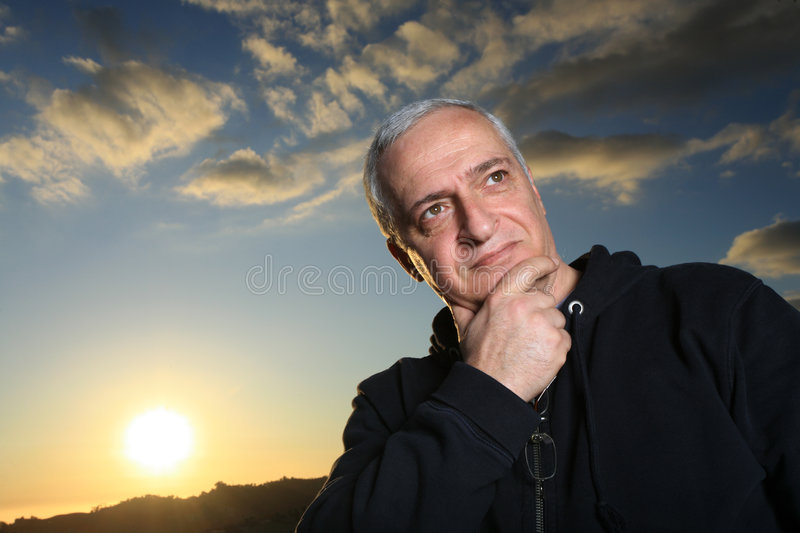 Mature man thinking. Mature man outdoors, thinking hard stock photography