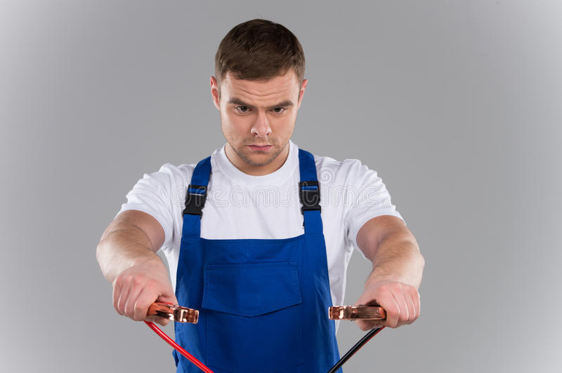 Mature man trying to connect jumper cables together. stock photography