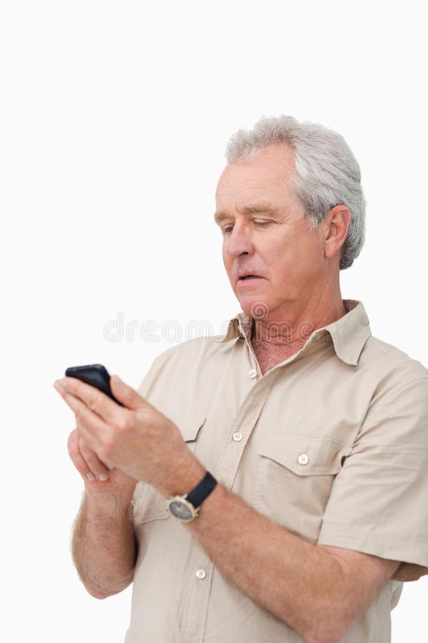 Mature Man Typing Text Message On His Cellphone Royalty Free Stock Images