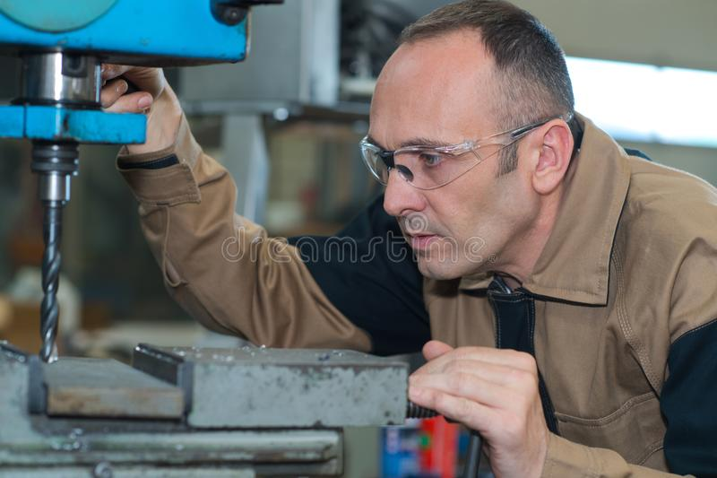 Mature man using drilling machine at industrial factory royalty free stock photos