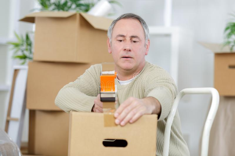 Mature man using duct tape for packing stuff in box. Man stock photos