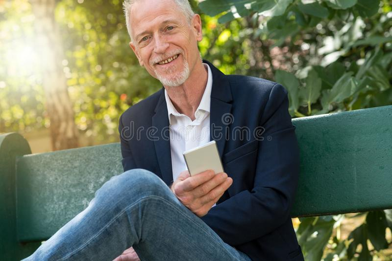Mature man using his mobile phone, light effect. Mature man using his mobile phone outdoors, light effect royalty free stock images