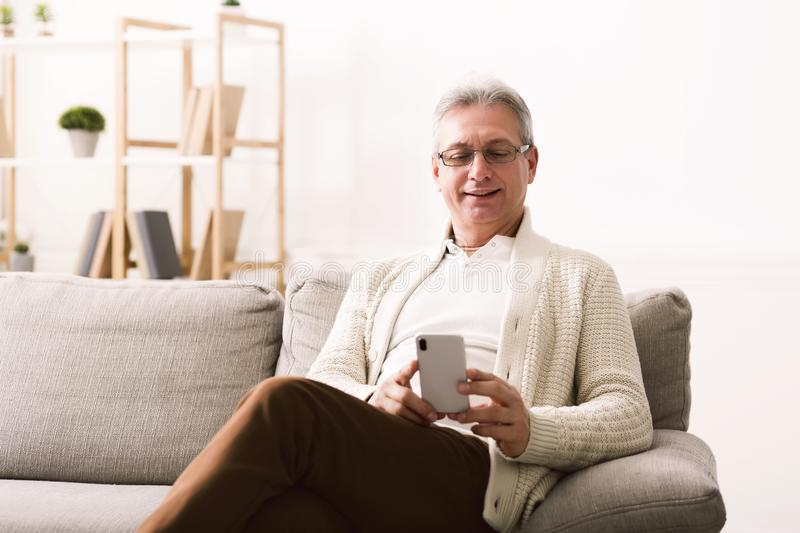 Mature man using smartphone, surfing internet at home stock photo