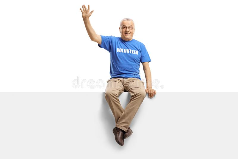 Mature man volunteer sitting on panel and waving royalty free stock images