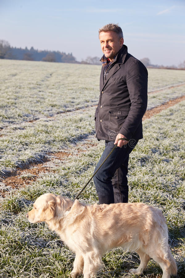 Mature Man Walking Dog In Frosty Landscape stock photo