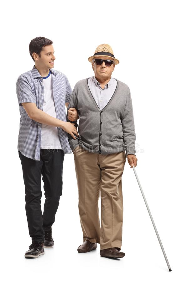 Mature man walking with the help of a young guy royalty free stock images