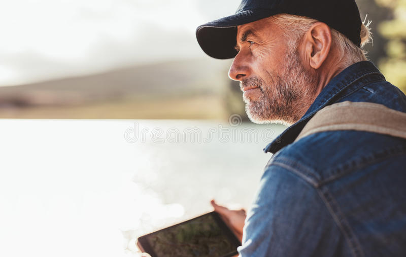 Mature man wearing cap sitting at a lake and looking at a view stock images