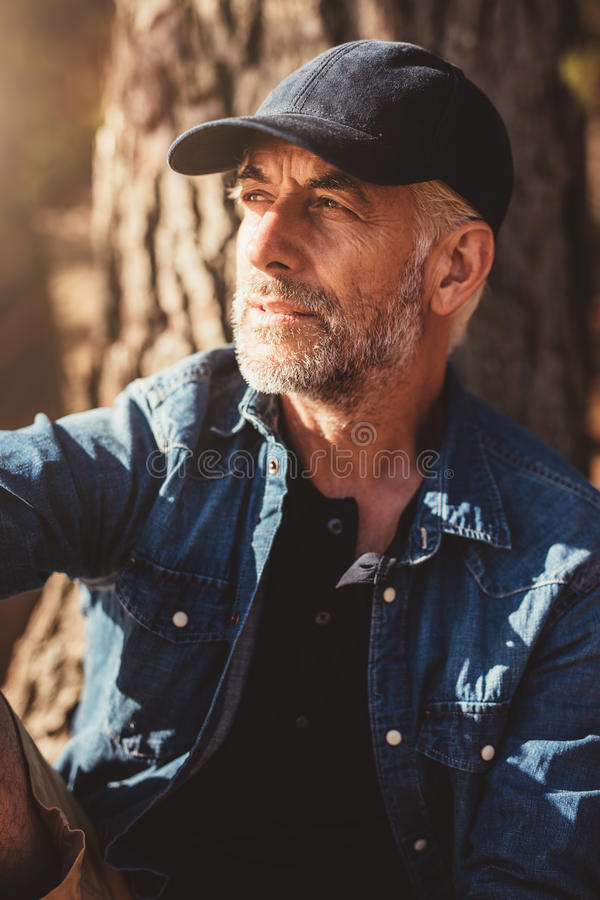 Mature man wearing cap sitting by a tree royalty free stock image