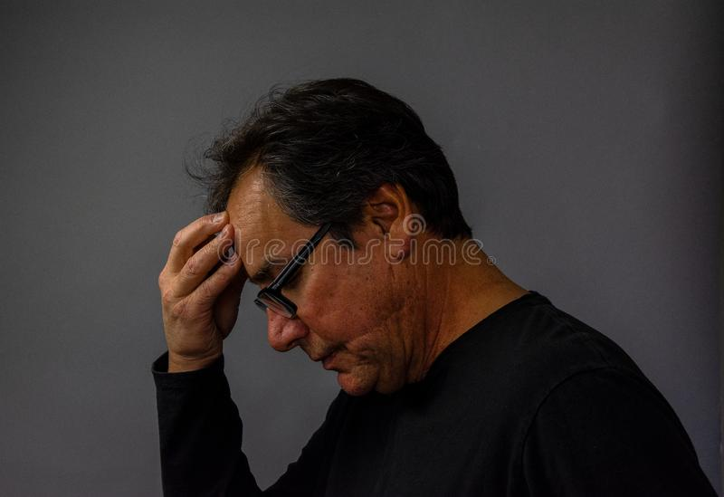 Mature man wearing glasses praying, contemplative, thinking. Despair. Religious, mental health, educational concepts stock photos