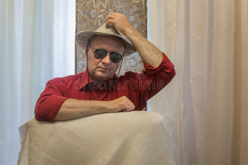 Mature man wearing hat and black sunglasses sitting and and lean elbow on chair back. Portrait of mature man wearing hat and black sunglasses sitting and and royalty free stock image