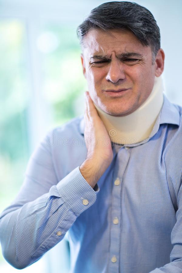 Mature Man Wearing Neck Brace Winces With Pain. Mature Man Wearing Neck Brace In Pain royalty free stock photography