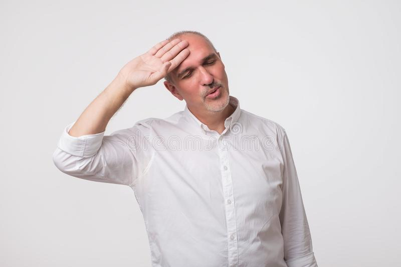 Mature man in white shirt looking exhausted. He with tired face wipes forehead. stock photo