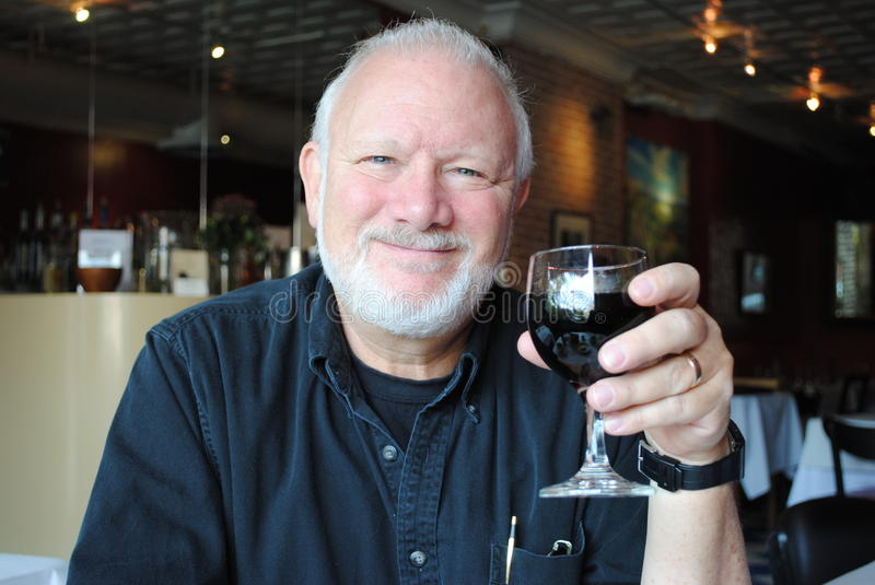 Mature Man with Wine. A happy mature man holding a glass of wine stock photo