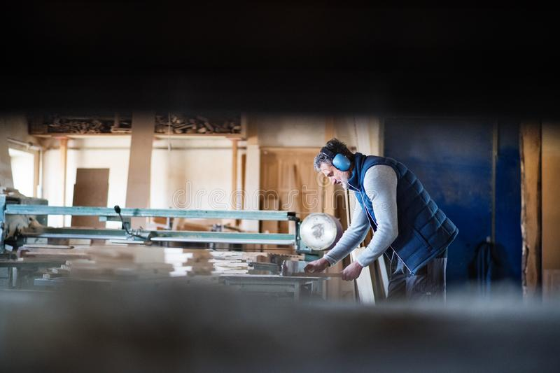 A man worker in the carpentry workshop, working with wood. stock image