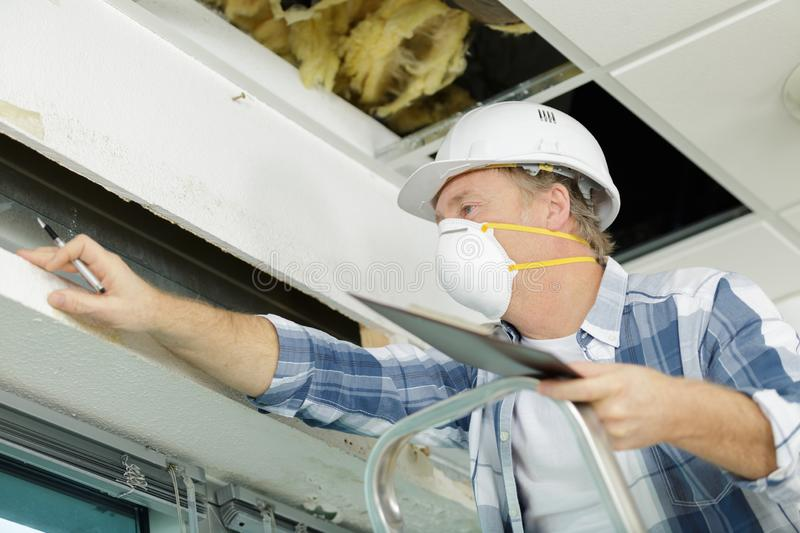 Mature man worker climbing into loft to insulate house roof. Man royalty free stock image