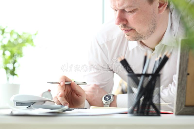 Mature man working with calculator evaluating financial opportunities for family vacation stock photos