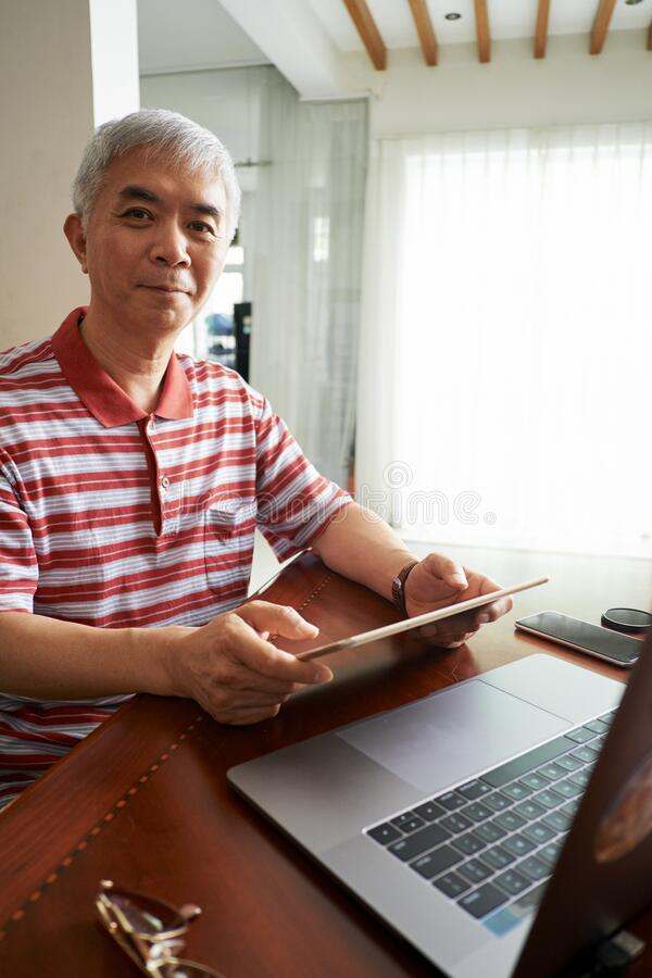 Mature man working from home stock images