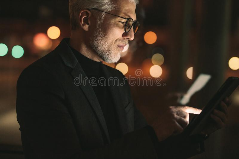 Mature man working late night in office stock image