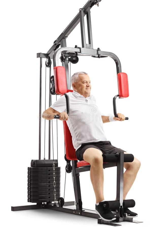 Mature man working out on a multifunctional exercise machine. Isolated on white background stock images